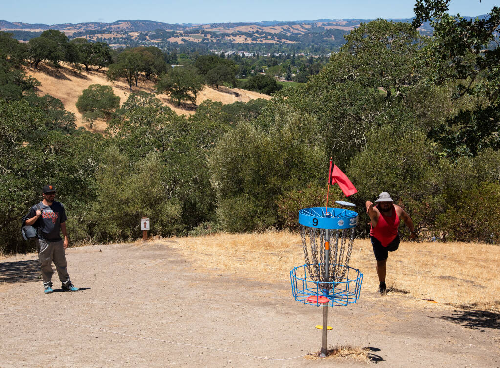 Mito Tellez, right, of Napa putts at scenic 9th Hole of the 18-hole disc golf course at Skyline Wilderness Park while Billy Murphy looks on, in Napa, Calif. on Saturday, June 12, 2021. (Alvin A.H. Jornada for The Press Democrat)