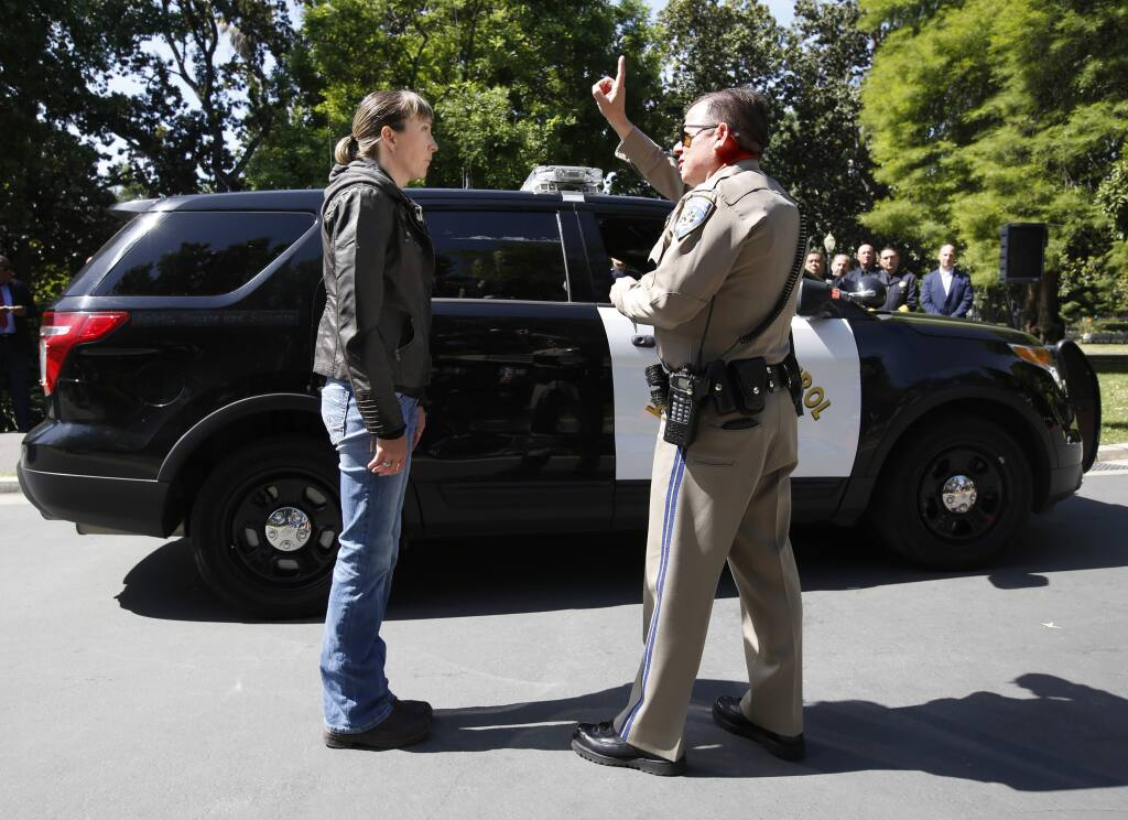 California Highway Patrol Officer Gary Martens, right, has CHP Sgt. Jaimi Kenyon, follow his finger during a demonstration of how drivers, suspected of impaired driving, are currently tested, Wednesday, May 10, 2017, in Sacramento, Calif. Three of California's largest counties are testing a device that can detect the presence of drugs in saliva within five minutes. Some officers and lawmakers want the devices used statewide after voters passed Proposition 64 in November, legalizing the recreational use of marijuana. (AP Photo/Rich Pedroncelli)