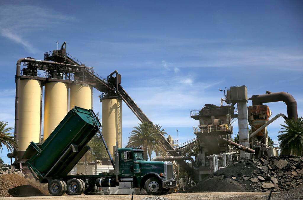 A dump truck unloads dirt and rock at the BoDean Company asphalt plant in Santa Rosa on Monday, June 10, 2019. (BETH SCHLANKER/ The Press Democrat)