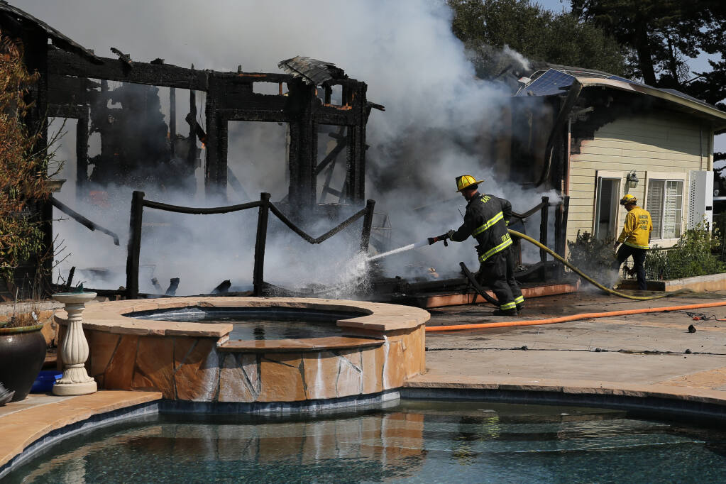 Rancho Adobe firefighter Casey Gray works to extinguish a fire at 487 Ormsby Lane in Petaluma on Tuesday, Sept. 21, 2021. (Beth Schlanker/The Press Democrat)