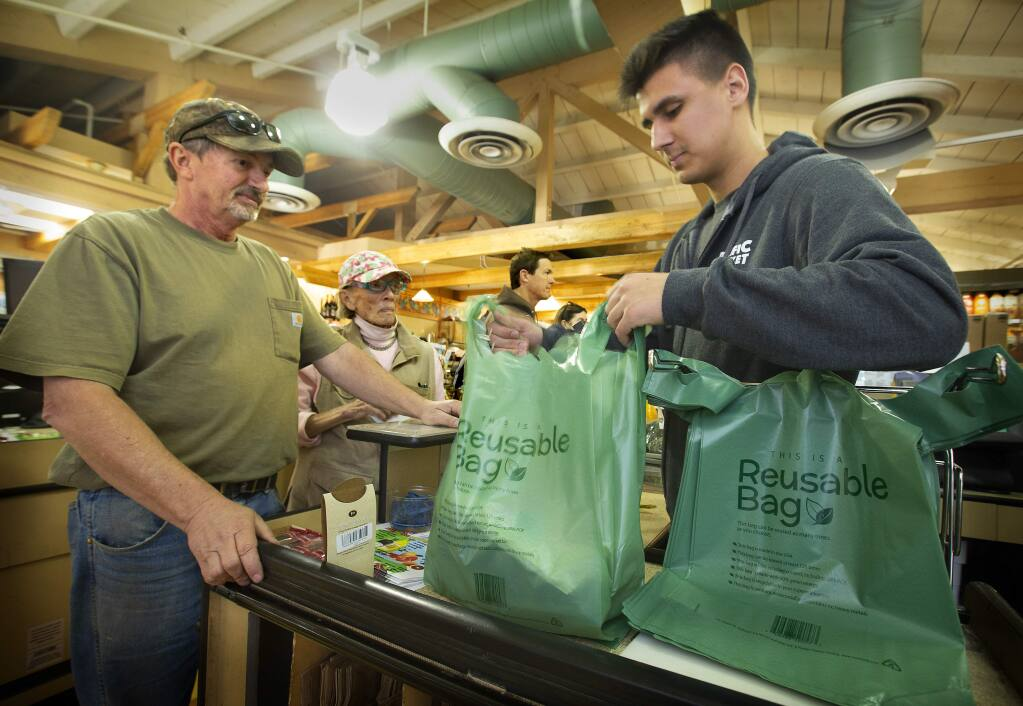 Checker Chris Leach uses a reusable plastic bag for customers Robert Evans, left, and Mary Smith at Pacific Market in Santa Rosa on Friday. (photo by John Burgess/The Press Democrat)