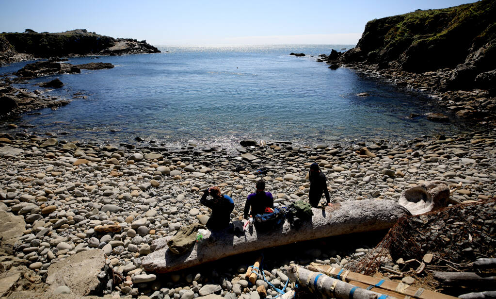 Chelsea Furr, 13, and her father Dan Furr with Eddie Kennedy of Woodland, relax after snorkeling in Gerstle Cove on the Sonoma coast at Salt Point, Saturday, March 13, 2021. Very little bull kelp remains in the cove,  (Kent Porter / The Press Democrat) 2021