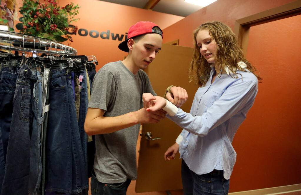 Social Advocates for Youth and Goodwill Industries of the Redwood Empire have teamed up to help out homeless teens with clothes. Taylor Wallace, left, helps his girl friend Megan Freeland pick out clothes for job interviews after she received clothing vouchers to be used at the Goodwill, Wednesday, November 5, 2014. (Crista Jeremiason / The Press Democrat)