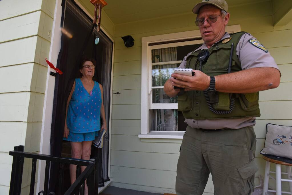 """""""I'm staying with my friend and kitty named Lily,"""" said Dana Cavallo, left, who refused to leave her home on University Avenue and defy a mandatory evacuation order as Bill Trunick, right, of the Sonoma County Regional Parks makes note of her refusal as he goes door to door Saturday in Healdsburg, California. October 26, 2019.(Photo: Erik Castro/for The Press Democrat)"""