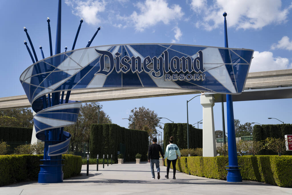 FILE - In this March 9, 2021, file photo, two visitors enter Disneyland Resort in Anaheim, Calif. (AP Photo/Jae C. Hong, File)
