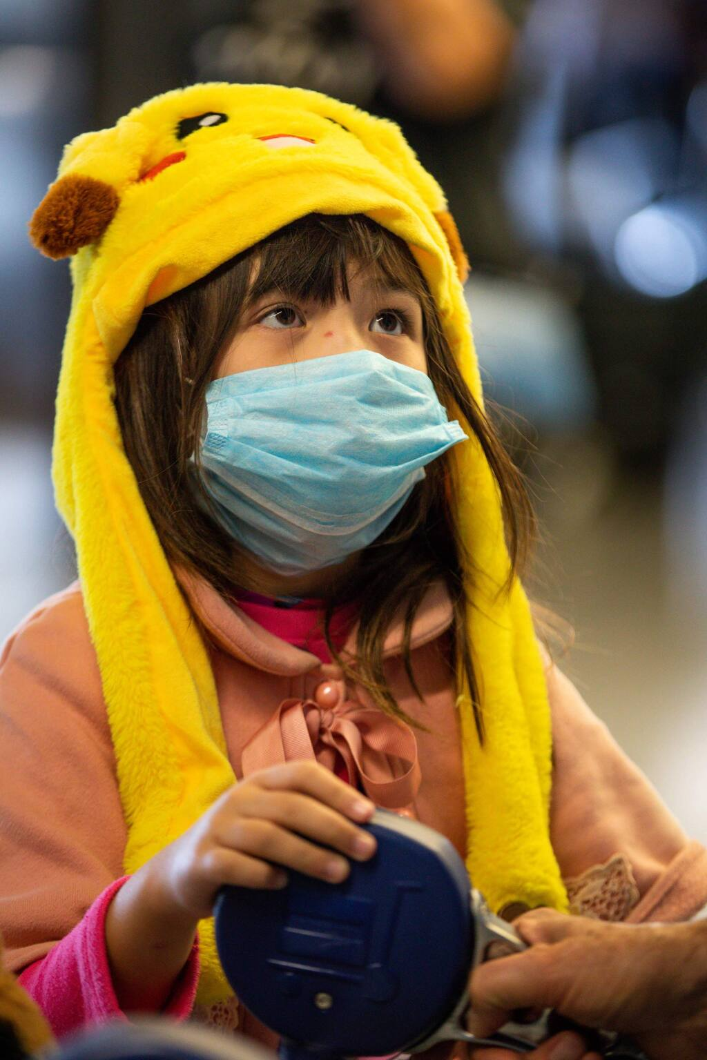 Daisy Johnston, 8, wears a face mask upon arriving to terminal G at San Francisco International Airport on Tuesday, Feb. 4, 2020. Daisy returned from China with her mother Amy Deng, who also wore a face mask because of the threat of the coronavirus. (Randy Vazquez/Bay Area News Group/TNS)