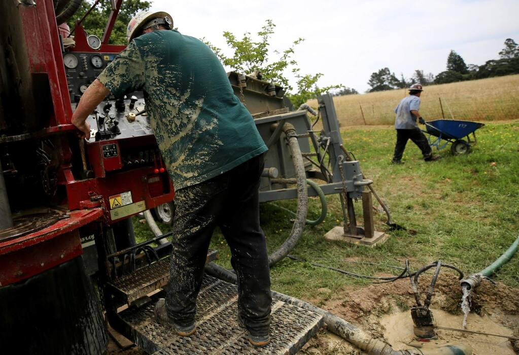 Robert Burgess, left, and Drake Coffey of Weeks Drilling & Pump Co.drill a residential water well near Cotati on Wednesday, June 7, 2017. (KENT PORTER/ PD)