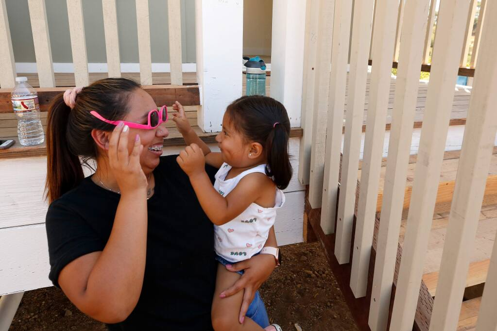 Estefani Cardenas plays with her daughter Mia, 2, before they walk through a house similar to the one being built for them, and other fire survivors, on the Medtronic Fountaingrove Campus, in Santa Rosa, California, on Friday, August 16, 2019. (Alvin Jornada / The Press Democrat)