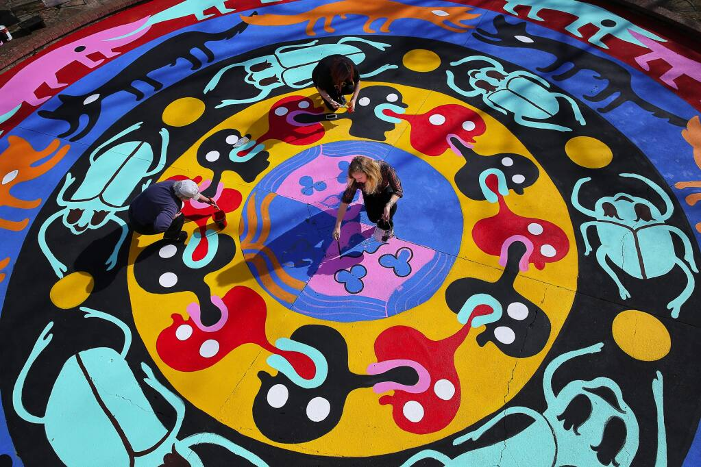 An artist who goes by the pseudonym Bud Snow, lower right, paints her mandala mural with the help of Judy Kennedy, left, and Reina Rivera at Juilliard Park, in Santa Rosa, on Wednesday, February 10, 2016. The mural was commissioned by the Santa Rosa Art in Public Places Committee with a grant from Downtown Connect.(Christopher Chung/ The Press Democrat)