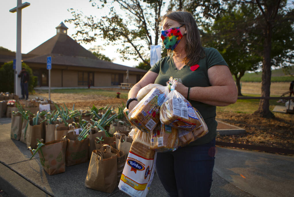 Lynne Gordon Moquete prepares bags for her nonprofit, Una-Vida's, weekly food giveaway, every Tuesday at Hillside Church of the Nazarene.(CRISSY PASCUAL/ARGUS-COURIER STAFF)