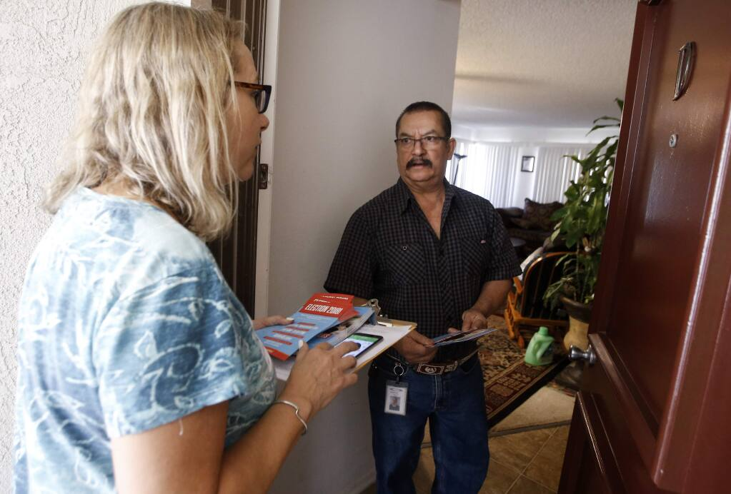 Democratic canvasser Maria Behan, left, from Swing Left Sonoma County talks with Fernando Perez, spreading the word for democratic candidates around the state in key areas to bolster the rolls of voters like for Katie Porter in Lake Forest, Calif., Saturday, Nov. 3, 2018. (for the Santa Rosa Press Democrat/AP Photo/Alex Gallardo)