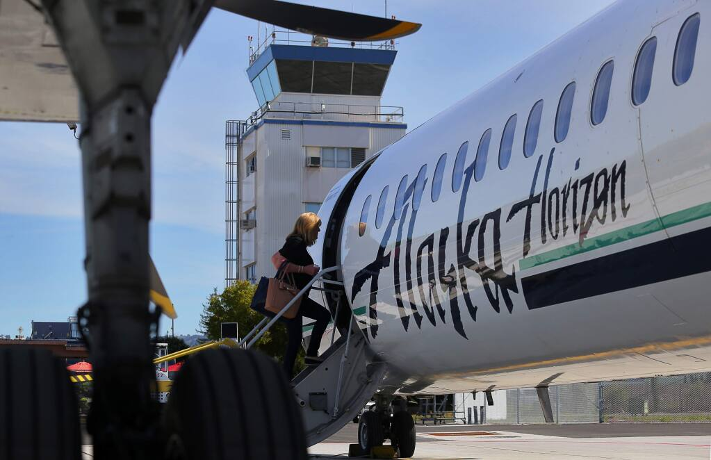 A passenger boards the Alaska Airlines inaugural flight to John Wayne Airport, in Orange County, from the Charles M. Schulz-Sonoma County Airport in Santa Rosa, on Wednesday, March 16, 2016. (Christopher Chung/ The Press Democrat)