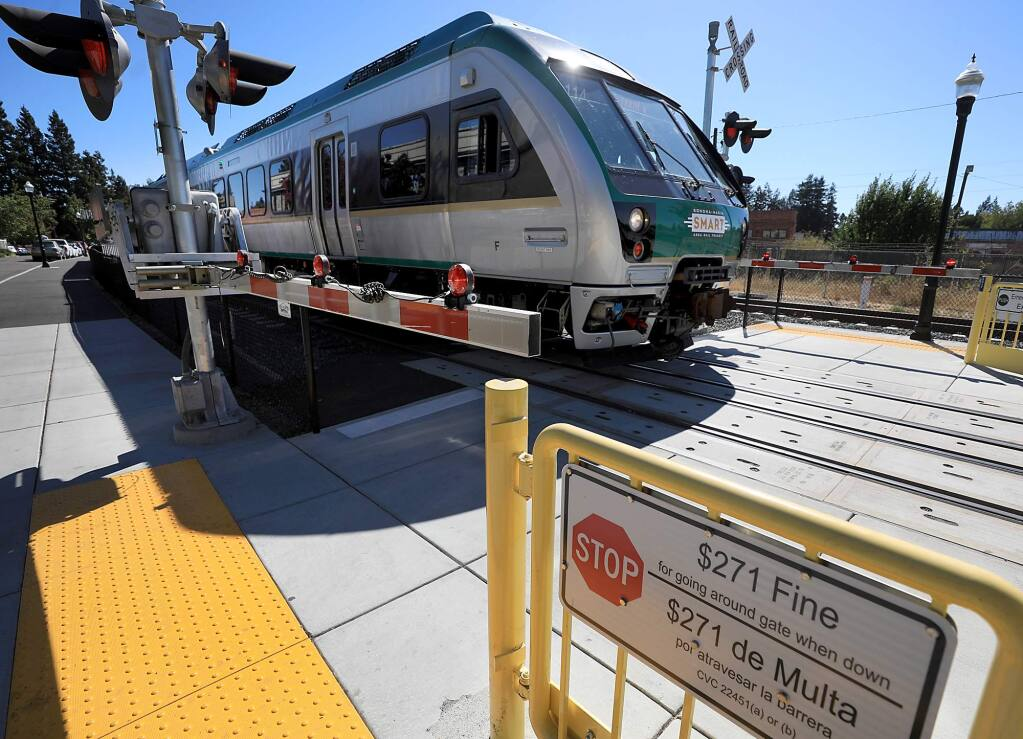 A pedestrian crossing arm is lowerd as a SMART train at the downtown Santa Rosa station in Railroad Square passes by, Monday, Sept. 10, 2018. (Kent Porter / The Press Democrat) 2018