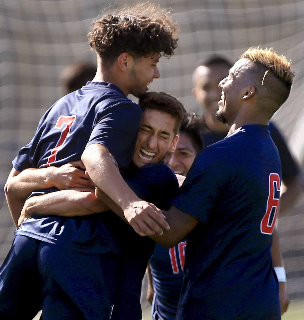 SRJC's Adrian Fontanelli, left, is congratulated by teammates Matias Gomez, middle, and Sergio Valenzuela after scoring the Bear Cubs' first goal within the first minute of play against the Contra Costa Comets, Wednesday, Sept. 4, 2019. (Kent Porter / The Press Democrat)