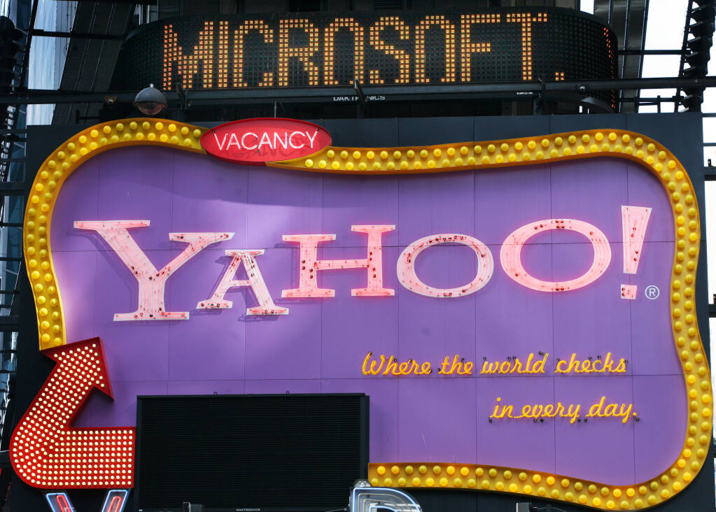 A Times Square news ticker flashes a headline about Microsoft above a billboard for Yahoo! in New York in this Friday, May 4, 2007 file photo. (AP Photo/Mark Lennihan, file)