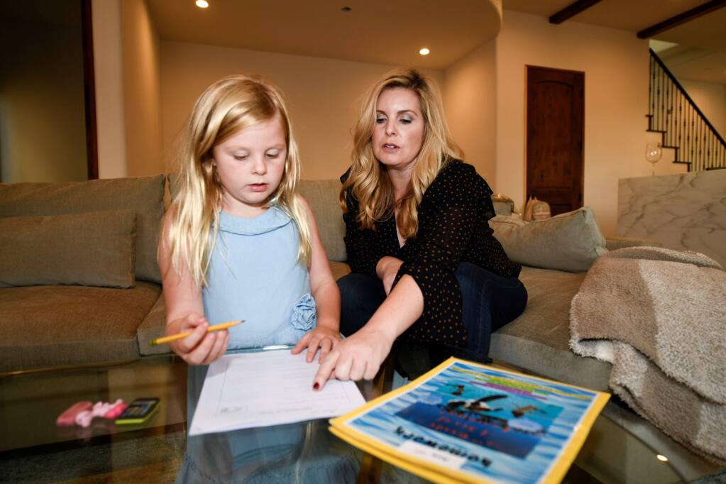 Kristy Militello, helps her daughter Ava with homework in the living room of their new home in San Diego. (Denis Poroy / For the Press Democrat)