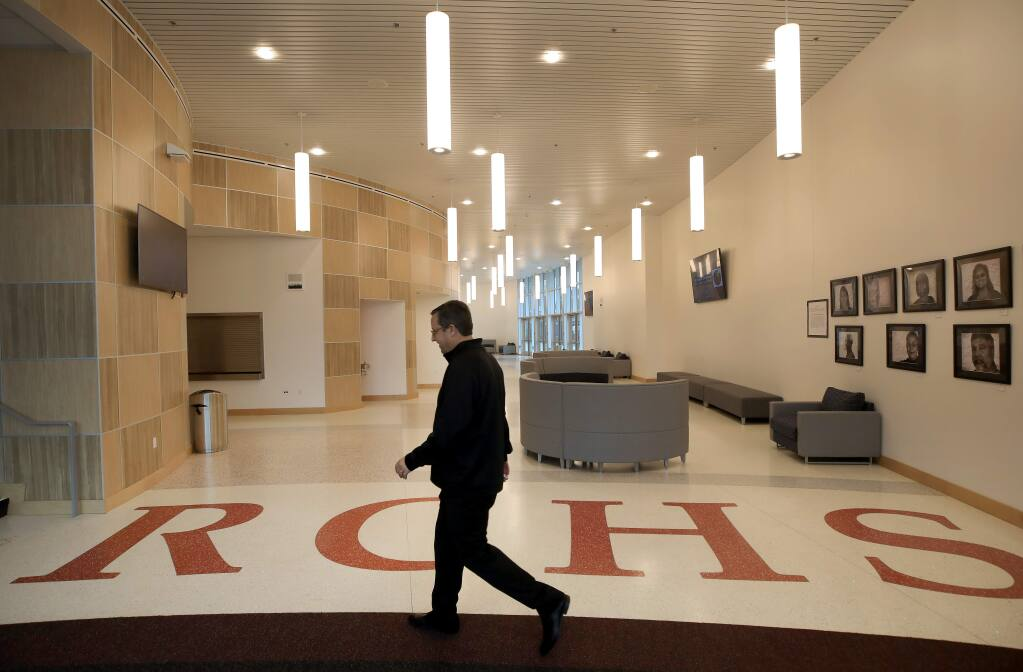 Rancho Cotate High School assistant principal Henri Sarlatte walks to open the theater doors, Thursday, Feb. 13, 2020, in a brand-new $52 million gymnasium and theater arts building on the campus in Rohnert Park. The gym is named after his father, Henry J. Sarlatte. (Kent Porter / The Press Democrat)