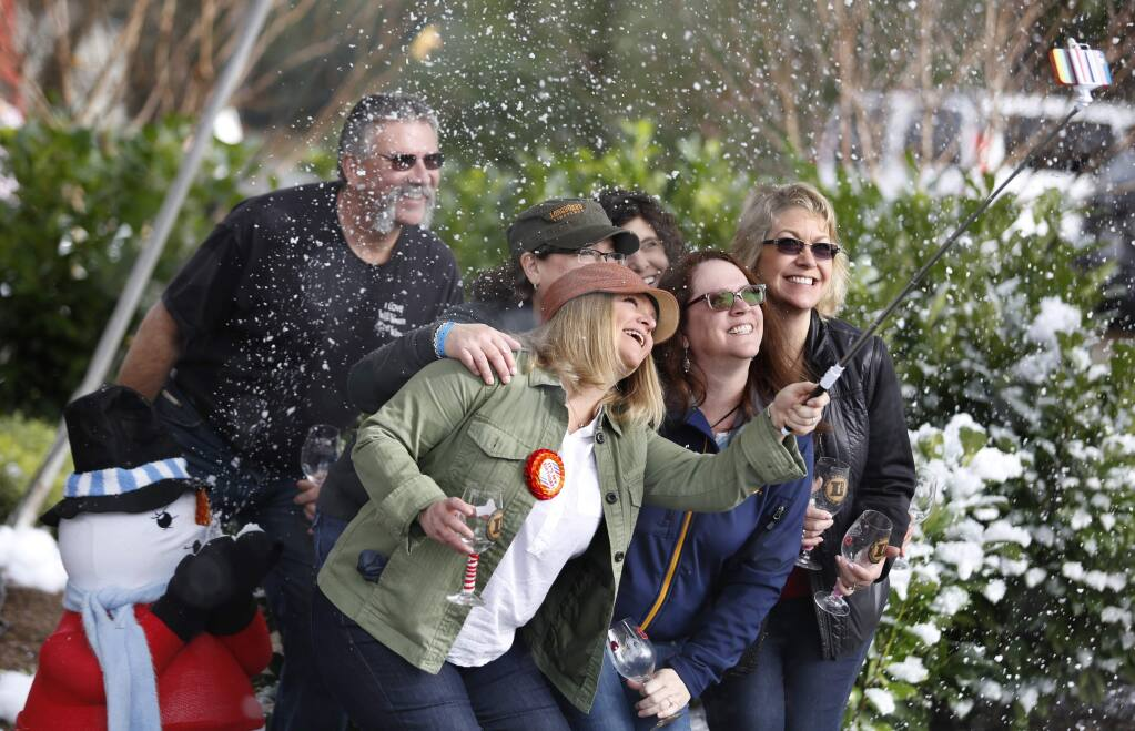 A group of friends use an extended selfie arm to take a photo of themselves as bubbles float around like snow at Chateau Diana as part of the 23rd Annual Winter WINEland event on Sunday, January 18, 2015 in Healdsburg, California . (BETH SCHLANKER/ The Press Democrat)