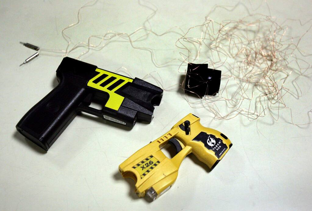 File Photo: Examples of two models of taser with a spent cartridge with fires 21 feet of insulated copper wire with two probes at the end.(John Burgess/PD)