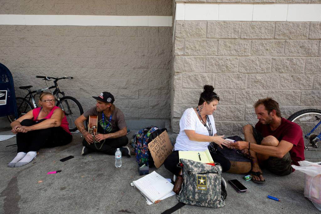 COTS homeless outreach specialist Cecily Kagy, second from right, encourages Jeffery Butler, right, to use some of the services COTS offers during a visit with him, Emily Morris-Jarboe, far left, and Joe Volavka where they congregate outside a Target store, in Rohnert Park, California, on Thursday, August 8, 2019. (Alvin Jornada / The Press Democrat)