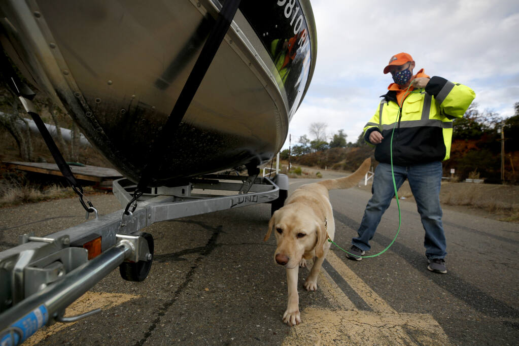 Beth Steinkraus leads the dog, Tugboat, around a boat to sniff for quagga and zebra mussels during an inspection at the boat ramp at Lake Sonoma north of Healdsburg on Tuesday, Dec. 15, 2020. (Beth Schlanker/ The Press Democrat)
