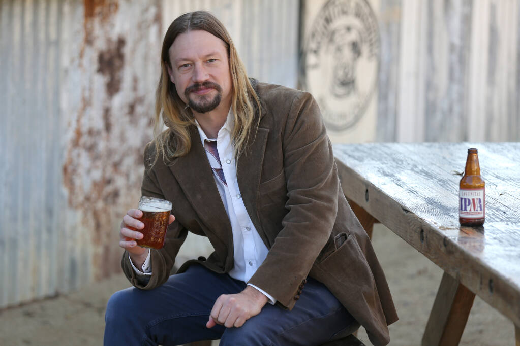 Jeremy Marshall, brewmaster at Lagunitas Brewing Company, holds a glass of the newly released non-alcoholic IPA on Dec. 1 in Petaluma. (BETH SCHLANKER/ The Press Democrat)