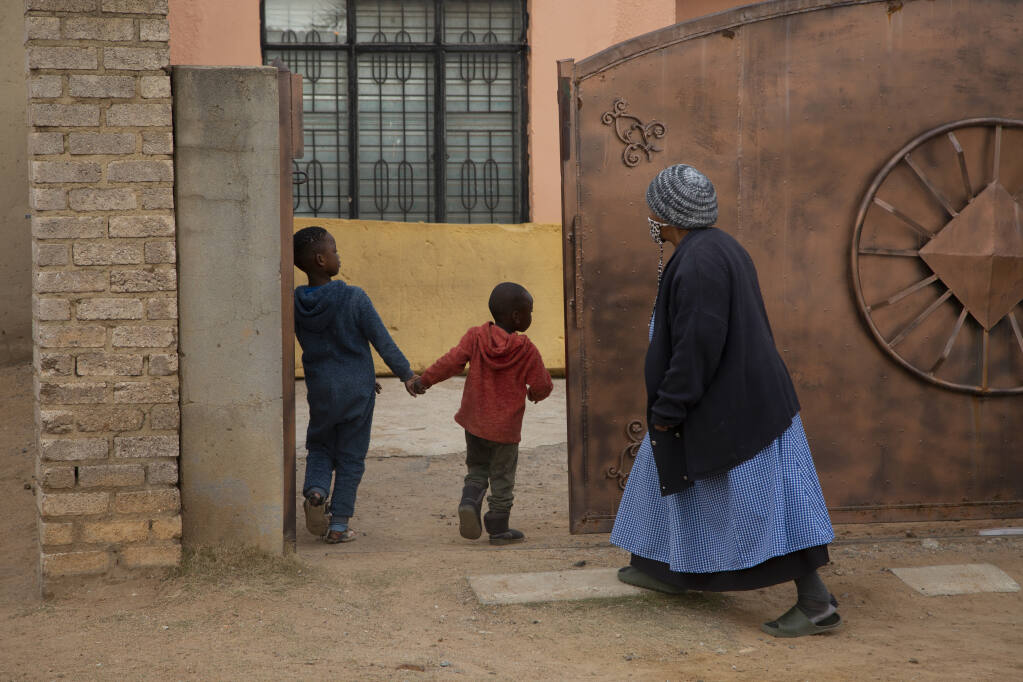 An elderly woman and children enter the property of the home of Gosiame Thamara Sithole in Tembisa, near Johannesburg Thursday June 10, 2021. South Africa is gripped by a mystery over if the woman, Sithole, has, as has been claimed, given birth to 10 babies in what would be a world-first case of decuplets.  The South African government said Thursday it is still trying to verify the claim. (AP Photo/Denis Farrell)