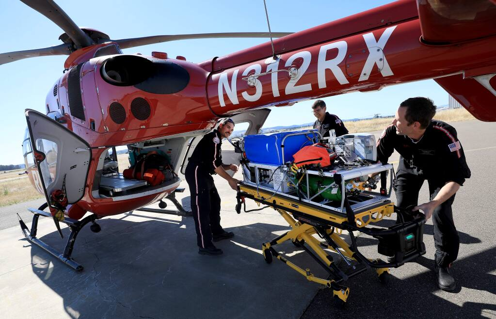 REACH Air Medical Services personnel, from left, flight nurse Parker Maloney, pilot Jeff Baker and flight paramedic David Hoytt, practice loading a portable incubator in one of the REACH helicopters at the Charles M. Schulz Sonoma County Airport, Friday, June 7, 2019. (Kent Porter / The Press Democrat) 2019