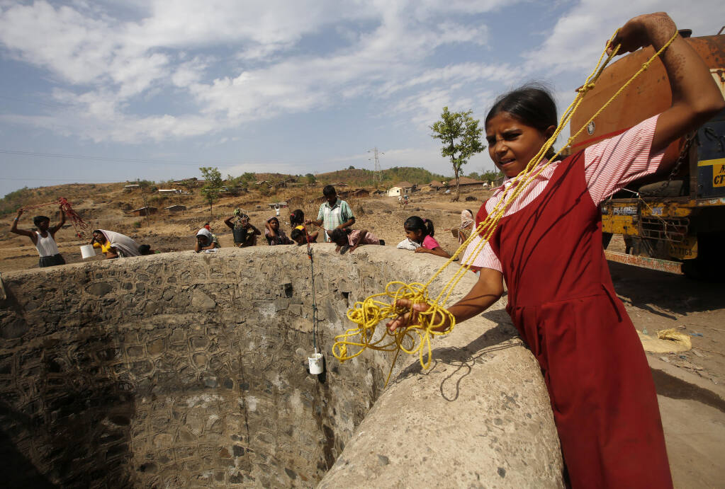 """FILE - In this May 4, 2016, file photo, a girl wearing her school uniform pulls a rope attached to a bucket as she tries to draw water after a tanker emptied water into a dried up well at Umber Maal village in Thane district in Maharashtra state, India.  Climate change could push more than 200 million people to move within their own countries in the next three decades and create migration hotspots unless urgent action is taken in the coming years to reduce global emissions and bridge the development gap, a World Bank report has found. The report published on Monday, Sept. 13, 2021 examines how long-term impacts of climate change such as water scarcity, decreasing crop productivity and rising sea levels could lead to millions of what the report describes as """"climate migrants"""" by 2050. (AP Photo/ Rajanish Kakade, File)"""