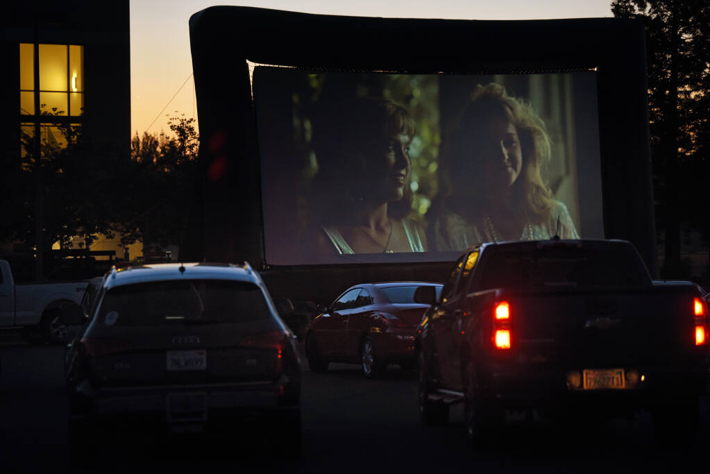 """Attendees in their vehicles watching """"Peggy Sue Got Married"""" during a drive-in movie fundraiser for Rep. Mike Thompson and the Santa Rosa-based Career Technical Education Foundation held at SOMO Village in Rhonert Park, Calif. on Saturday, May 1, 2021.(Photo: Erik Castro/for The Press Democrat)"""