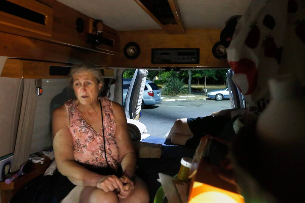 'We are not the face of homelessness that everyone sees. We dont need a handout; we just need a hand up, a safe place to get back on our feet again,' says Marilee Diehl referring to the safe parking program. Illuminated by a camping lantern, Marilee sits in her van at one of the designated safe parking lots for the homeless in Santa Rosa, California, on Saturday, July 15, 2017. (Alvin Jornada / The Press Democrat)