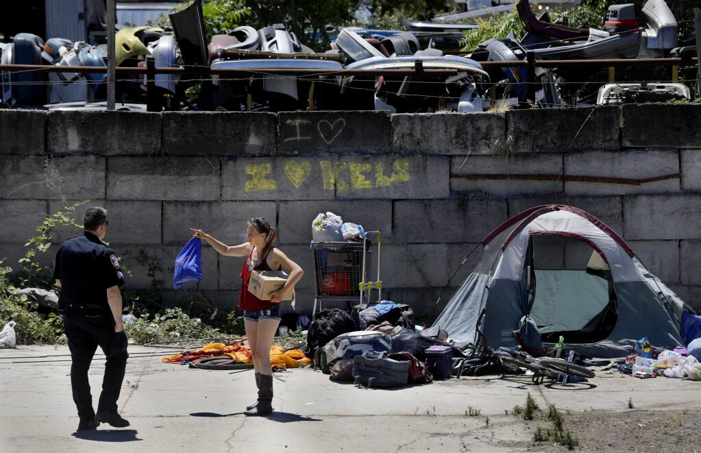 Homeless woman Merry Potter talks with Santa Rosa Police Sgt. Jonathan Wolf as police evict more than two dozen homeless people from a camp off the Joe Rodota Trail near Roberts Ave in Santa Rosa on Thursday, June 21, 2018. (Beth Schlanker/ The Press Democrat)