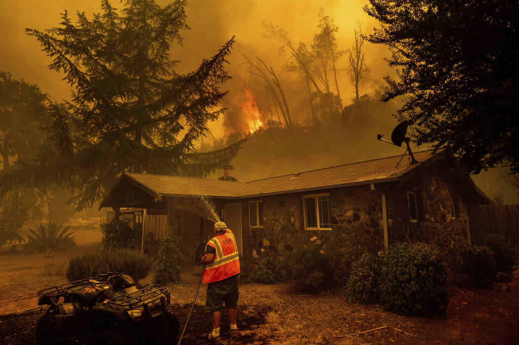 FILE - In this Aug. 18, 2020, file photo, Jerry Kuny sprays water on a home as flames from the LNU Lightning Complex fires approach in unincorporated Napa County, Calif. This home remained standing as the main front passed although the fire went on to destroy multiple residences.  (AP Photo/Noah Berger, File)