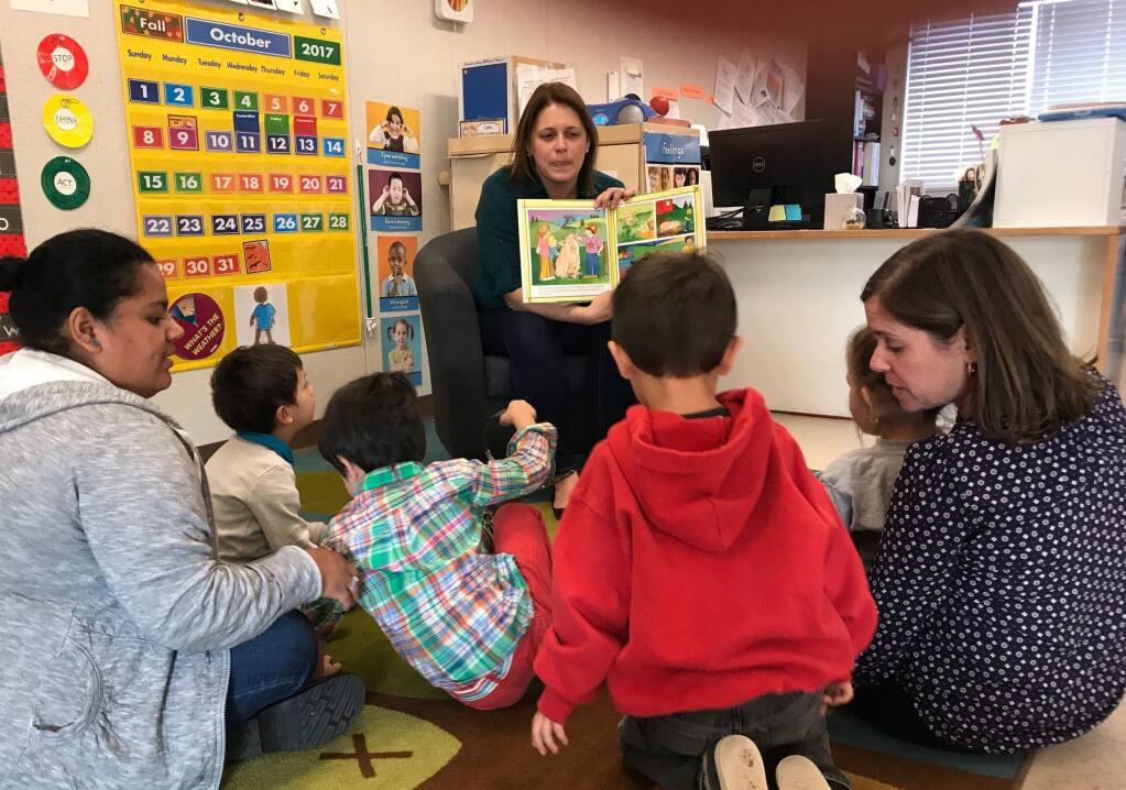 Kelly Bass Seibel, Petaluma Health center's director of business development and partnership, reads to kids at North Bay Children's Center.