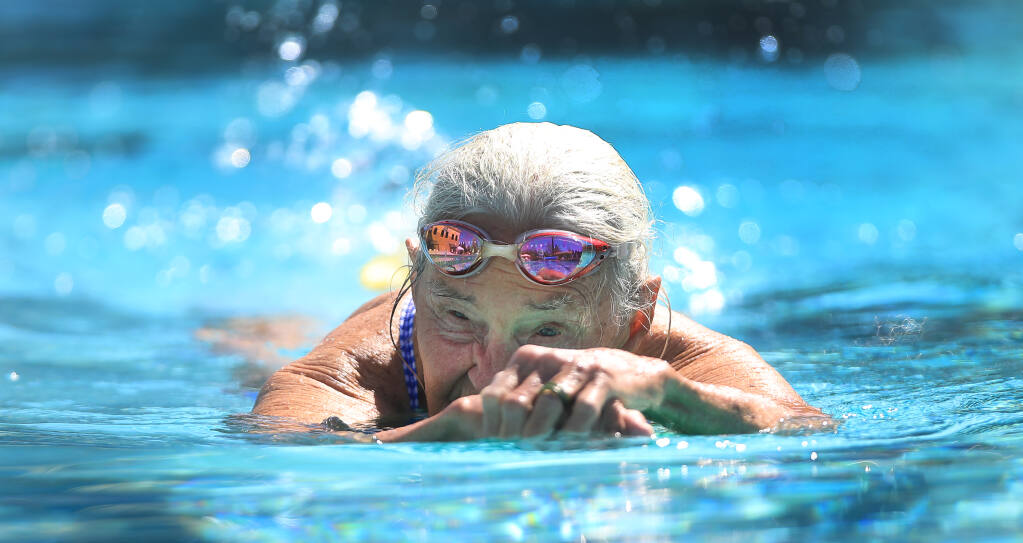 At 91 years old, Gail Roper uses a paddleboard to get limbered up and works out several days a week at a Healdsburg pool. Roper has been swimming since her teen years, and also appeared in the 1952 Olympic Games. Photo taken Thursday, March 25, 2021, in Healdsburg. (Kent Porter / The Press Democrat)