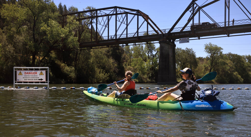 Laura Duffy, left, of Sonoma and Jodi Wilson of Petaluma, kayak upstream from a sign warning boaters not to go down stream from the Wohler Bridge due the replacement of the rubber dam that can only be done during summers low flow on the Russian River, Friday, June 25, 2021 near Forestville.  (Kent Porter / The Press Democrat) 2021