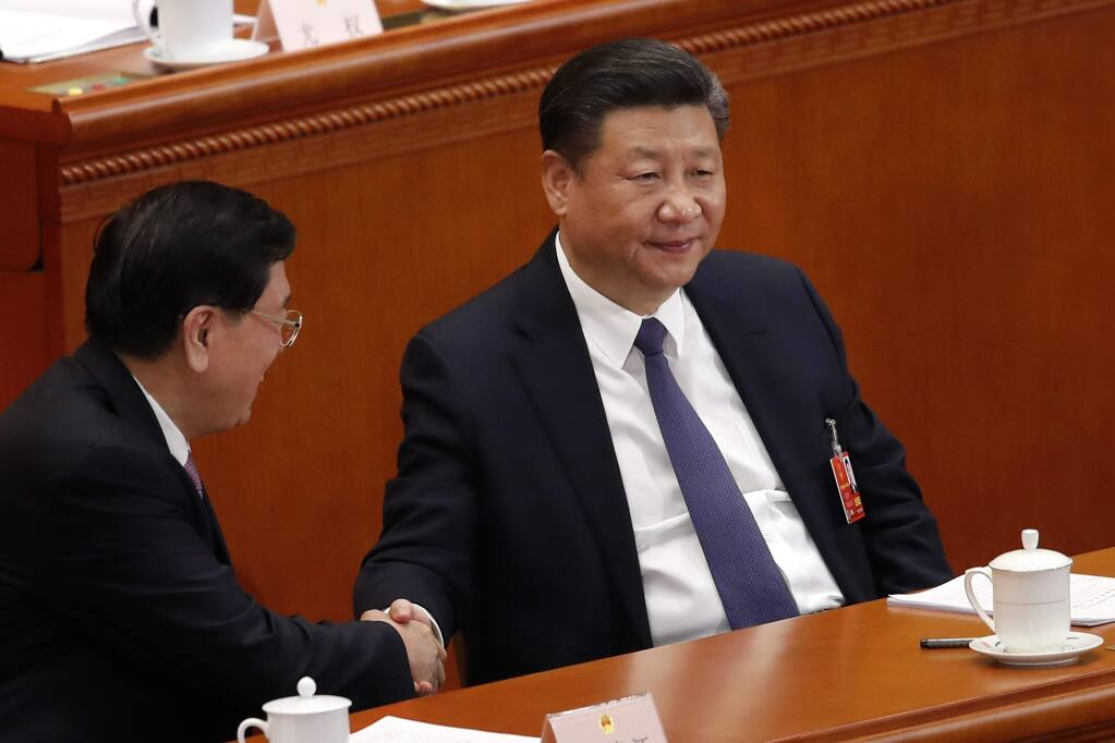 Chinese President Xi Jinping, right, shakes hands with National People's Congress Chairman Zhang Dejiang during a plenary session of the National People's Congress at the Great Hall of the People in Beijing, Sunday, March 11, 2018. China's rubber-stamp lawmakers on Sunday passed a historic constitutional amendment abolishing presidential term limits that will enable Xi to rule indefinitely. (AP Photo/Andy Wong)