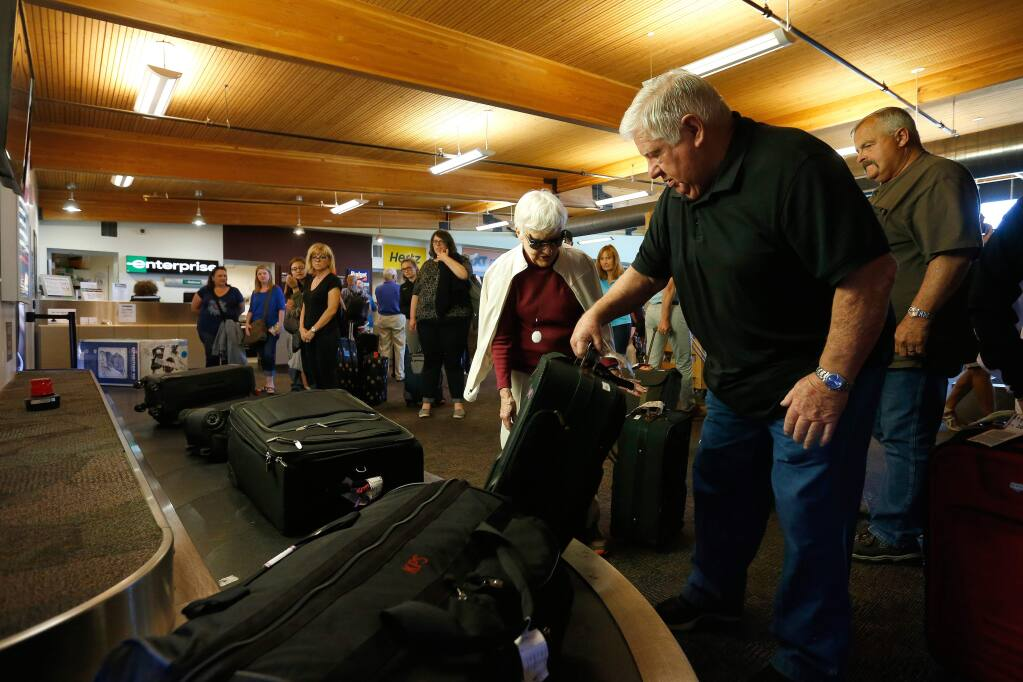 Former Santa Rosa resident Tom McGee, right, now of Peoria, Illinois, helps Marlene Miller of Tucson, Arizona pull her suitcase off the single luggage conveyor that currently services all four airlines flying into Charles M. Schulz-Sonoma County Airport in Santa Rosa, California, on Tuesday, July 11, 2017. Airport officials are planning to double the size of Gate 2, add more parking spaces and build a new 28,000 square foot terminal in the future. (Alvin Jornada / The Press Democrat)