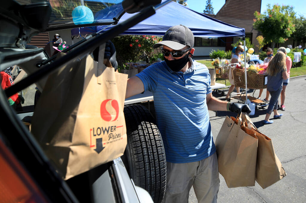 Steve Stiles places groceries in to a vehicle during a food giveaway at Elisha's Pantry in Santa Rosa, Thursday, July 30, 2020. (Kent Porter / The Press Democrat) 2020