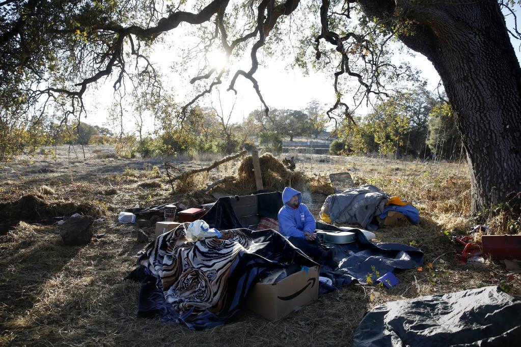 Ron Stamp, who is homeless, smokes a cigarette at his campsite along the Petaluma River in Petaluma on Monday, Nov. 23, 2020. (Beth Schlanker / The Press Democrat)