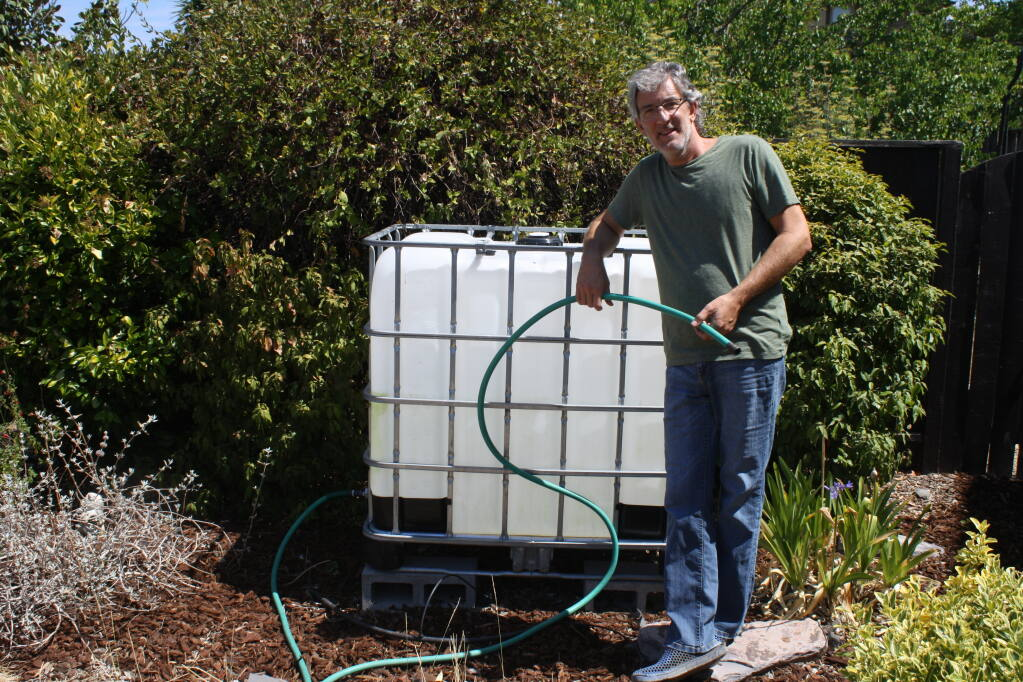 Patrick Ronsche stands next to a water tank at his Healdsburg home near Simi Winery. He uses it store free recycled water delivered by city of Healdsburg contract water truck haulers once a week. He uses the water to restore a small front lawn and plants in the yard. Some 700 Healdsburg residents have signed up for this program reducing the need for potable water by 54%. (Gary Quackenbush / for North Bay Business Journal)