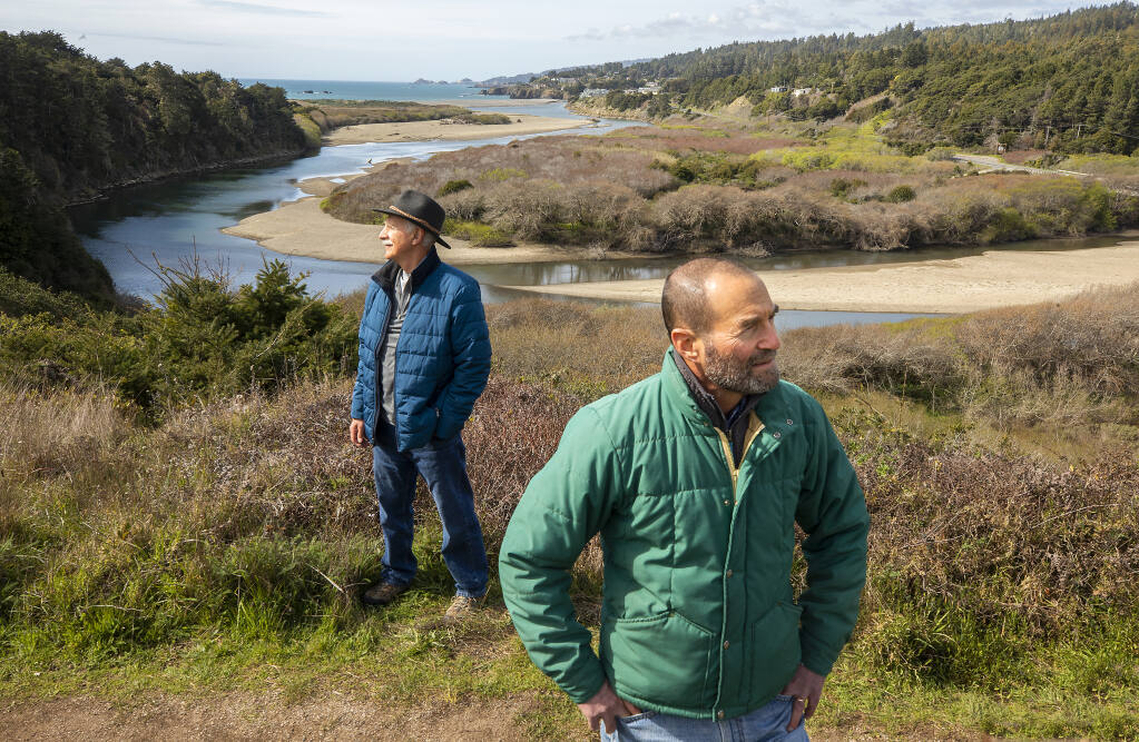 Dave Shpak, Mill Bend project manager, right, and John Walton, vice president of the Redwood Coast Land Conservancy board, stand on a bluff overlooking the mouth of the Gualala River and  the 113-acre Mill Bend Preserve recently acquired by the group on Wednesday, March 17, 2021.   (Photo by John Burgess/The Press Democrat)