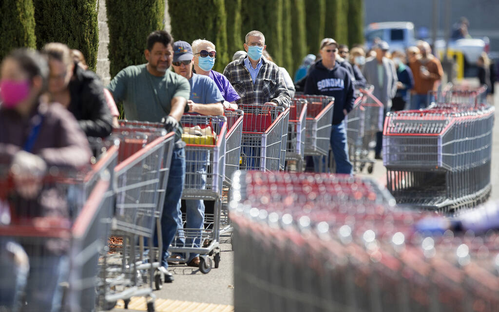 Shoppers wait in line spaced 6 feet apart at the Santa Rosa Costco on Friday, April 3, 2020. The line stretched around the building, and patrons waited up to 45 minutes to enter the store as personnel controlled the total number of people in the store at one time.   (John Burgess / The Press Democrat)