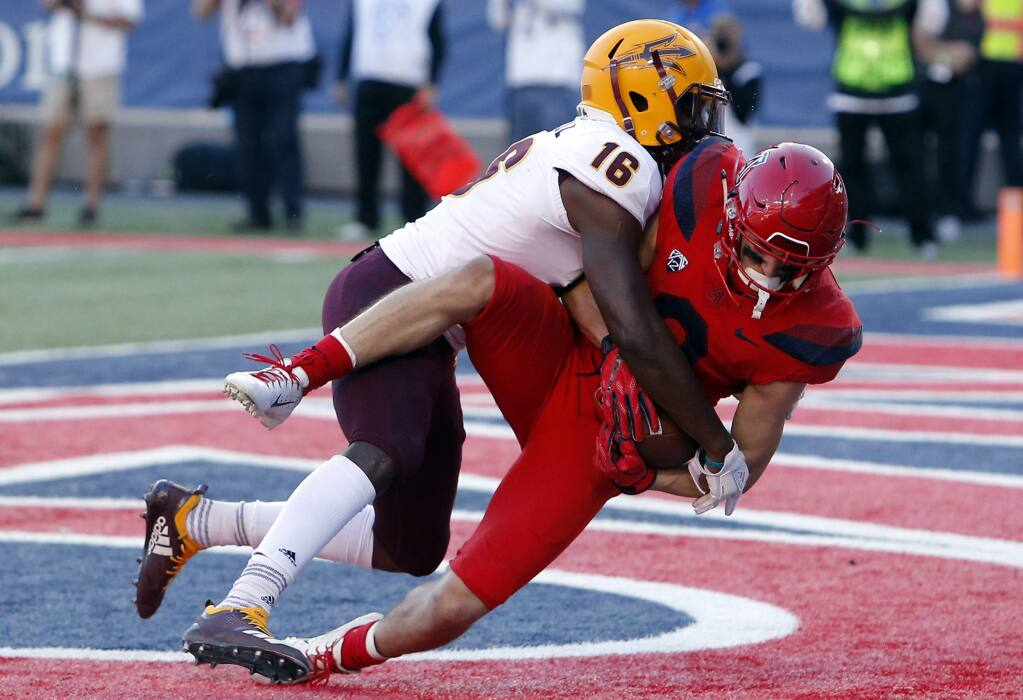 Arizona wide receiver Tony Ellison, right, holds onto the football after getting hit by Arizona State safety Aashari Crosswell (16) for a touchdown in the second half during an NCAA college football game, Saturday, Nov. 24, 2018, in Tucson, Ariz. (AP Photo/Rick Scuteri)