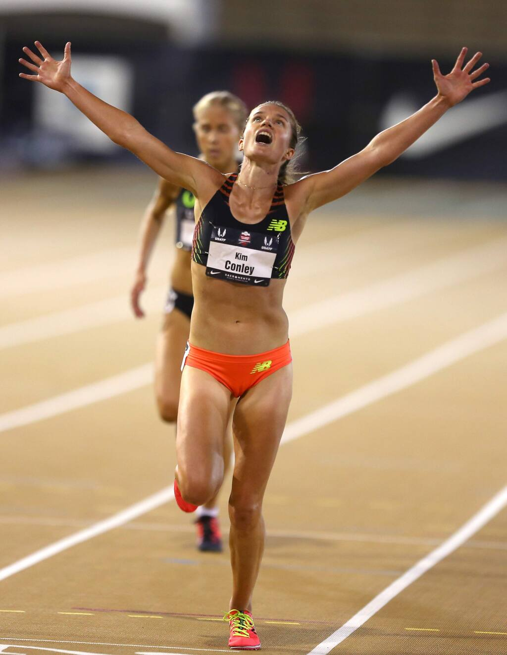 Kim Conley throws her arms up in celebration as she wins the 10,000-meter race at the USA Track and Field Outdoor Championships in Sacramento on Thursday, June 26, 2014. (Christopher Chung / The Press Democrat)