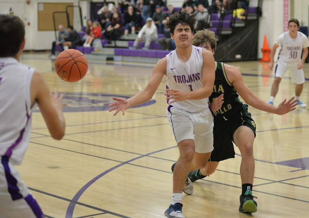 SUMNER F0WLER/FOR THE ARGUS-COURIEREven a crash from behind can't stop Petaluma's Esteban Bermudez from delivering an accurate pass. The Trojans are counting on the junior not only to shoot, but be a ball distributor as well.
