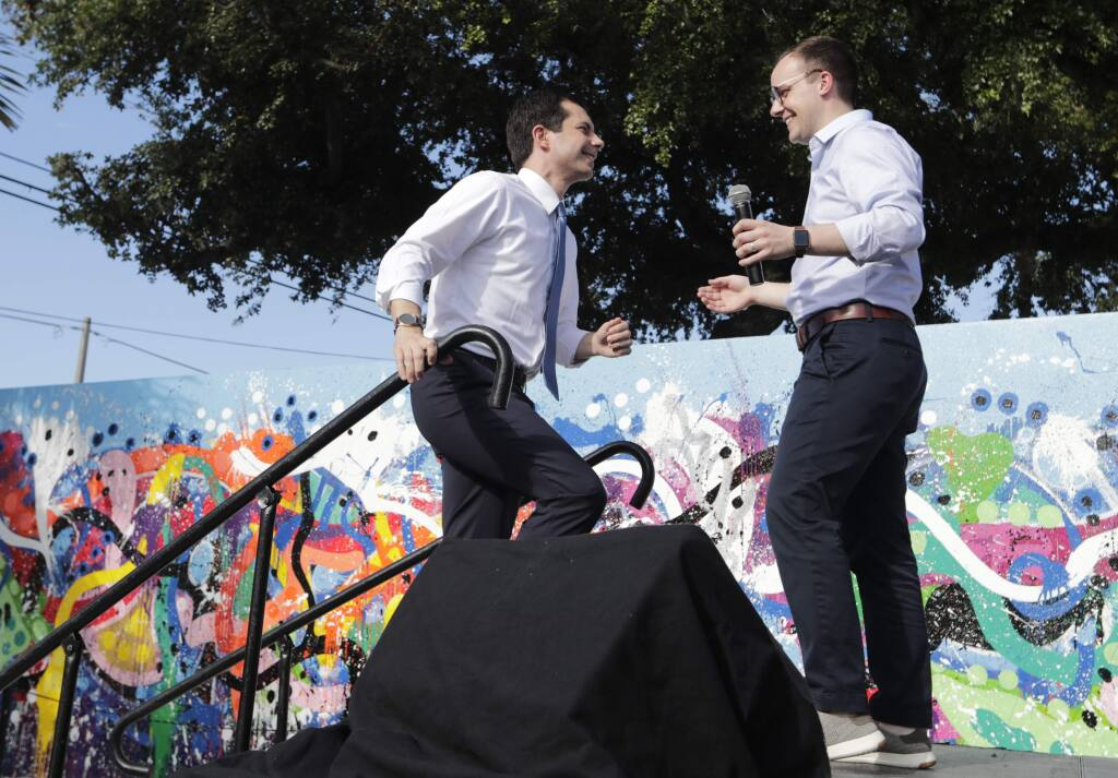 In this May 20, 2019, file photo, Democratic presidential candidate Pete Buttigieg, the mayor of South Bend, Ind., left, is introduced by his husband Chasten Buttigieg, right, during a fundraiser at the Wynwood Walls, in Miami. Buttigieg knows firsthand the burden of six-figure student loan debt. He and his husband have loans of more than $130,000, placing them in the ranks of the 43 million Americans who owe federal student debt.(AP Photo/Lynne Sladky, File)
