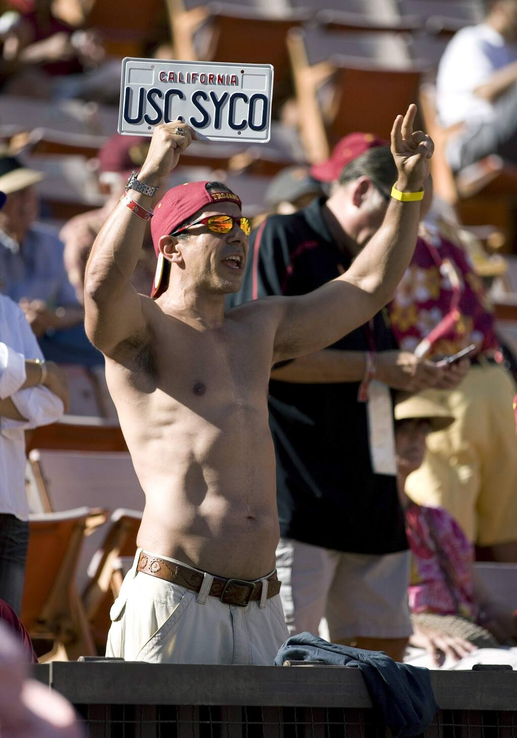 FILE - In this Sept. 2, 2010 file photo Roy Nwaisser, of Los Angeles, cheers during an NCAA college football game between the University of Southern California and Hawaii at Aloha Stadium in Honolulu. Nwaisser has four degrees from the University of Southern California and is a super fan of its storied football squad - he hasn't missed a home or away game in 27 years. But his devotion has been tested by a series of scandals culminating with the school's starring role in a massive college admissions bribery case that is the latest disgrace threatening to tarnish USC's hard-fought reputation as an academic, as well as athletic, powerhouse. (AP Photo/Eugene Tanner,File)