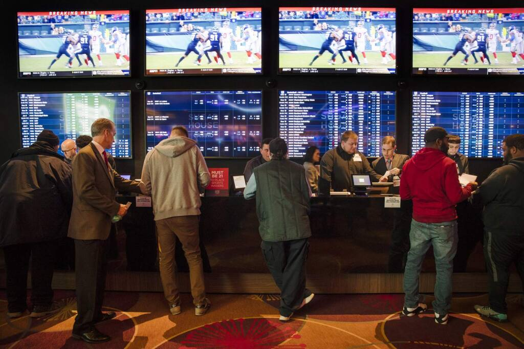 """FILE - In this Thursday, Dec. 13, 2018, file photo, gamblers place bets in the temporary sports betting area at the SugarHouse Casino in Philadelphia. The federal government would regulate sports betting nationwide under a bill to be introduced Wednesday, Jan. 19,2018. The bill would have the U.S. Justice Department set minimum standards states must meet in order to offer sports betting, but denies the sports leagues the so-called """"integrity fees"""" they have been seeking in new legislation, essentially a cut of sport betting revenue. (AP Photo/Matt Rourke, File)"""