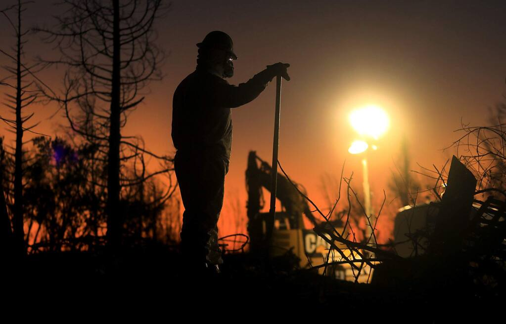 A crew from Argonaut Constructors of Santa Rosa work in to the night to clear debris from a razed home on Hillary Court in Coffey Park, Monday Nov. 6, 2017, one month after the Tubbs fire roared through Santa Rosa. (Kent Porter / The Press Democrat) 2017